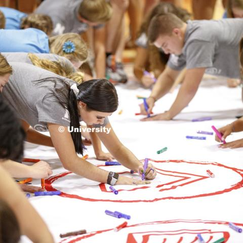 Students trace their hand and sign their name to a huge banner at the Learning Community Welcome Event in the rec center. The banner will hang in Abel Sandoz Residence Center for the school year. August 17, 2018. Photo by Craig Chandler / University
