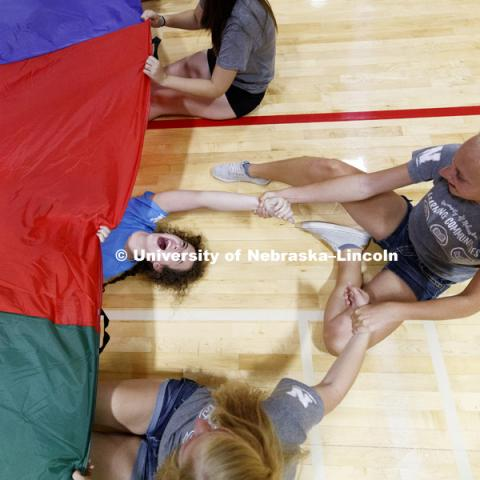 Hope Blomenberg laughs as she is rescued from being pulled under the parachute during a game of Chute Shark. She is in the pre-vet Learning Community. Learning Community Welcome Event in the rec center. August 17, 2018. Photo by Craig Chandler /