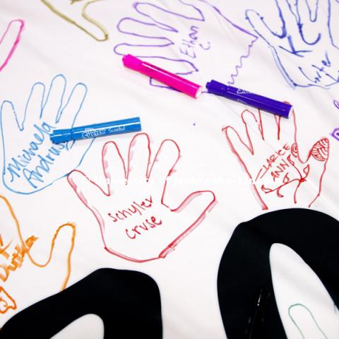 Learning Community members trace their hands on the Learning Community Banner. The banner will hang in Abel Sandoz Residence Center for the school year. Learning Community Welcome Event in the rec center. August 17, 2018. Photo by Craig Chandler /
