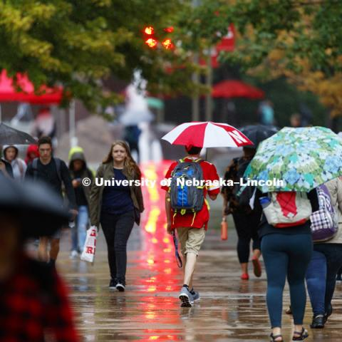 Students battle the rain as they cross campus to their first day of classes. August 20, 2018. Photo by Craig Chandler / University Communication