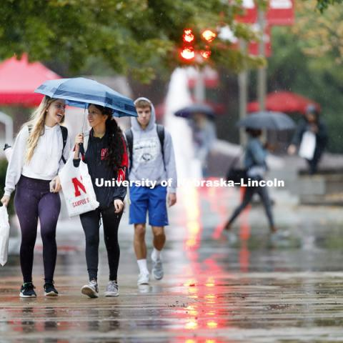 Katie Whittaker of Papillion and Gisselle Hernandez of Dakota City, South Dakota, share an umbrella and a conversation on the first day of classes. August 20, 2018. Photo by Craig Chandler / University Communication.