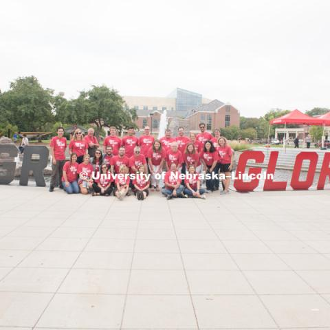 The University Communication group poses for a picture in front of the Broyhill Fountain by the Grit and Glory signs. In Our Grit, Our Glory brand reveal party on city campus at the Nebraska Union. August 30, 2018. Photo by Greg Nathan, University Communication.