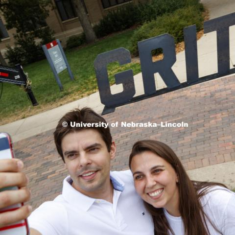 Felipe Ribeiro and Thais Ribeiro take a selfie in front of the Grit stand out. In Our Grit, Our Glory brand reveal party on east campus at the Nebraska Union. August 31, 2018. Photo by Craig Chandler / University Communication.