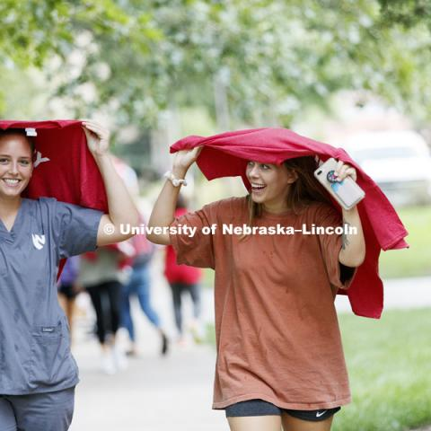Leah Sackschewski and Katie Whittaker found quick use of their new In Our Grit, Our Glory brand reveal party on east campus at the Nebraska Union. August 31, 2018. Photo by Craig Chandler / University Communication.