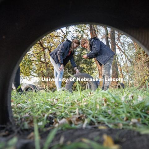 Amy Douglas of Kansas City and Taylor Pitzer of Omaha photograph a scale on tire treads as part of collecting evidence. FORS 400 Crime Scene Investigation. Forensics class works at the site of an old house on the north side of east campus. October 22, 2018. Photo by Craig Chandler / University Communication.