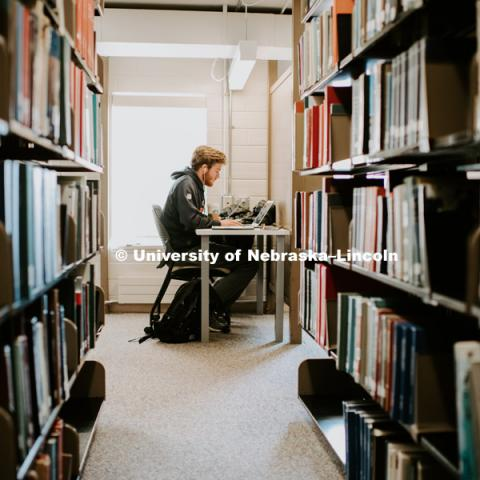 Student Studying in the stacks at Love Library. December 9, 2018. Photo by Justin Mohling, University Communication.