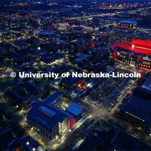 Memorial Stadium is a big red anchor to the colorful city campus Thursday night. At lower left is the College of Business. Center left is the Nebraska Union. Glow Big Red bathes the campuses with red lights as part of N150's Charter Week celebration. February 14, 2019. Photo by Craig Chandler / University Communication.