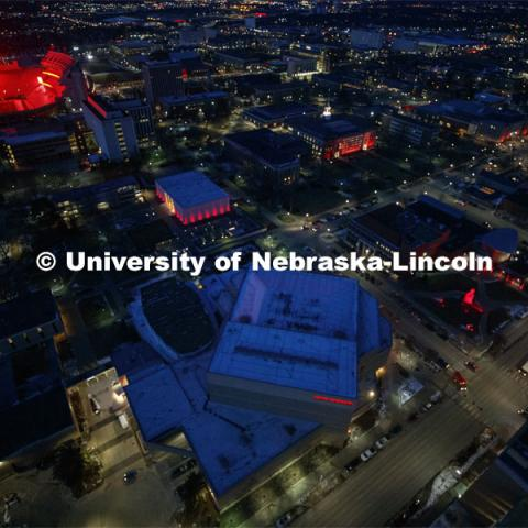 Memorial Stadium is a big red anchor to the colorful city campus Thursday night. At lower left is the Lied Center. Above the Lied is the Sheldon Art Museum and in the center is Love Library. Glow Big Red bathes the campuses with red lights as part of N150's Charter Week celebration. February 14, 2019. Photo by Craig Chandler / University Communication.