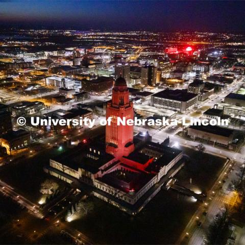 The Capitol glows red with the university to the above right in the photo. Glow Big Red bathes the campuses with red lights as part of N150's Charter Week celebration. February 14, 2019. Photo by Craig Chandler / University Communication.