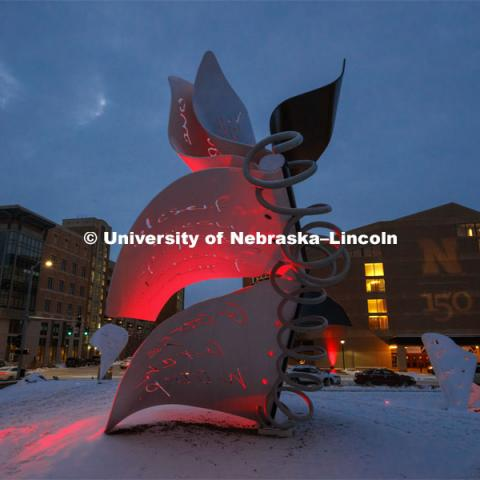 The Torn Notebook sculpture between the Lied and the visitor's center glows red and is surrounded by fresh-fallen snow. Glow Big Red bathes the campuses with red lights as part of N150's Charter Week celebration. February 15, 2019. Photo by Craig Chandler / University Communication.