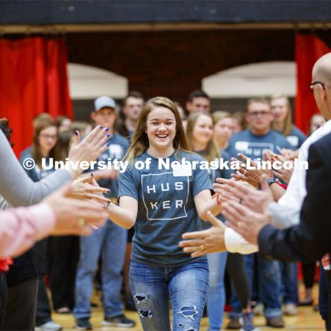 Madison Nuss runs through a tunnel walk of high-fives at the FFA signing ceremony for current senior FFA members who have committed to Nebraska. April 3, 2019. Photo by Craig Chandler / University Communication.