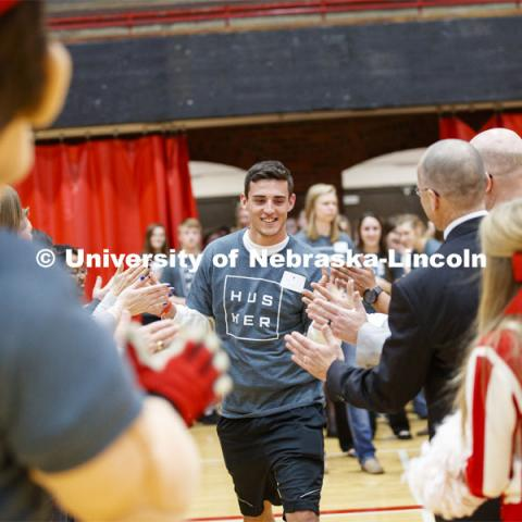Seth George runs through a tunnel walk of high-fives at the FFA signing ceremony for current senior FFA members who have committed to Nebraska. April 3, 2019. Photo by Craig Chandler / University Communication.