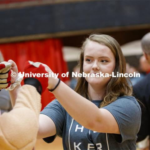 Kelsey Schlichtman fist bumps Herbie Husker as she runs through a tunnel walk of high-fives at the FFA signing ceremony for current senior FFA members who have committed to Nebraska. April 3, 2019. Photo by Craig Chandler / University Communication.