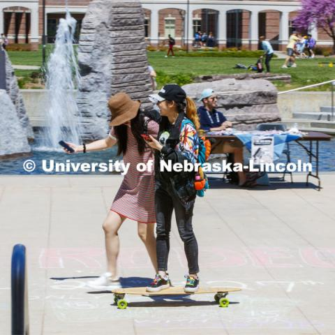 Hanchen Zhang gets a free ride on her skateboard as her friend, Sihui Li walks her along the plaza by the fountain. April 24, 2019. Photo by Craig Chandler / University Communication.