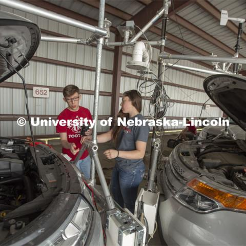Nebraska students (from left) Brennan Darrah and Maddy Diedrichsen discuss how to attach instrumentation to the front of a mesonet (storm chase) vehicle during prep work for the TORUS project. April 26, 2019. Photo by Troy Fedderson / University Communication
