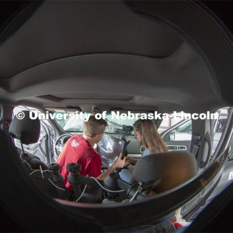 Nebraska students (from left) Brennan Darrah and Maddy Diedrichsen install a new computer screen inside a storm chase vehicle. Each of the research vehicles include three computer stations — two in the back seats and one in the front. Along with collecting data, the computers are also used to track storms via radar and for navigation. April 26, 2019. Photo by Troy Fedderson / University Communication