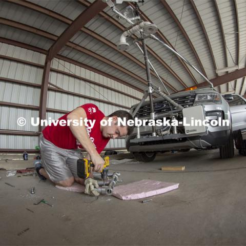 Graduate student Alex Erwin drills a pipe that will hold an instrument cluster on Nebraska's newest storm chase vehicle. Starting this spring, 13 Huskers will be part of TORUS, a national study designed to collect data about how severe storms and tornadoes are formed. April 26, 2019. Photo by Troy Fedderson / University Communication