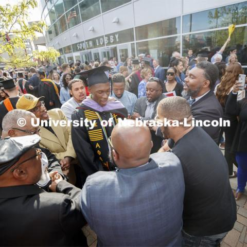 Friends, family and fellow Alpha Phi Alpha fraternity brothers form a circle around Davielle Phillips outside the arena following commencement. Phillips earned dual degrees of MBA and Master of Architecture. 2019 Spring Graduate Commencement in Pinnacle Bank Arena. May 3, 2019. Photo by Craig Chandler / University Communication