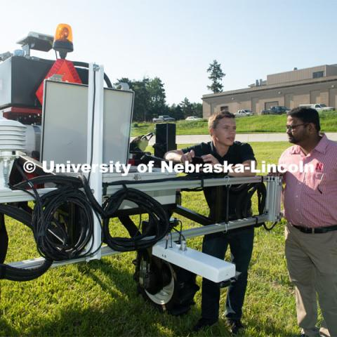 Grad student Josh Murman is with Santosh Pitla, associate professor of advanced machinery systems in the Department of Biological Systems Engineering at the University of Nebraska–Lincoln. Pitla is currently developing an autonomous tractor using ground robotics. Pitla and his team are testing their driverless tractor on the tractor testing field on East Campus. The autonomous tractors are named Flexible Structured Robotic Vehicle (FlexRo), the tractor is currently used for plant phenotyping, which is measuring the physical characteristics of the plant. According to Pitla, cameras are added to the machine to collect images that characterize plant conditions. Photo for the 2019 publication of the Strategic Discussions for Nebraska magazine. June 10, 2019, Photo by Gregory Nathan / University Communication.