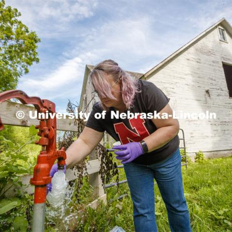 Jodi Sangster, a post-doc civil engineer specializing in environmental engineering, takes a water sample from the well spigot of Jeanne Hevner's Martell, Nebraska, land. July 1, 2019. Photo by Craig Chandler / University Communication.
