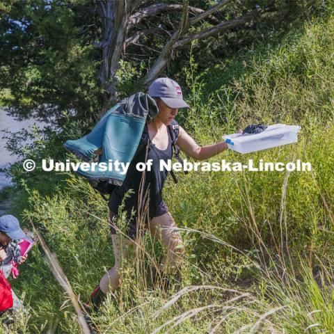 Kayla Vondracek and Sydney Kimnach work their way back from the Niobrara River after sampling a site. Jessica Corman, assistant professor in the School of Natural Resources, UCARE research group researching algae in the Niobrara River. Fort Niobrara National Wildlife Refuge. July 13, 2019. Photo by Craig Chandler / University Communication.