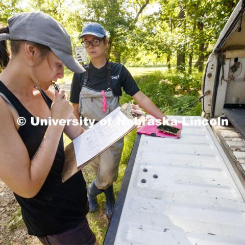 Kayla Vondracek and Sydney Kimnach look over their data after sampling a site. Jessica Corman, assistant professor in the School of Natural Resources, UCARE research group researching algae in the Niobrara River. Fort Niobrara National Wildlife Refuge. July 13, 2019. Photo by Craig Chandler / University Communication.