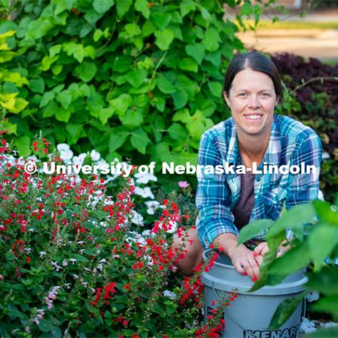 Ann Powers Research Technician, Agronomy and Horticulture, works in the Backyard Farmer Gardens. Today she is using a technique called deadheading to stimulate growth of new blossoms. August 6, 2019. Photo by Gregory Nathan / University Communication.