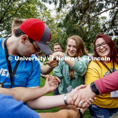 Kyle Harris of Elkhorn, NE, Brandy Kinnander of Armsrong, IA, and Anastasia Paitz of Waverly, NE, try to untangle themselves from a human knot as part of an ice-breaker at the First Husker Welcome. August 18, 2019. Photo by Craig Chandler / University Communication.
