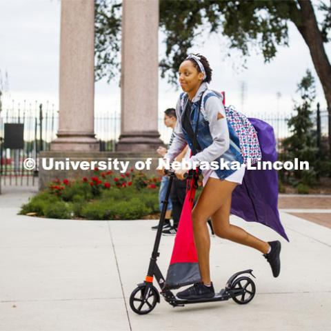 Alissa Clarke is loaded down with her flag team gear as she scooters her way to Wednesday evening's Cornhusker Marching Band practice in Memorial Stadium. City Campus. August 21, 2019. Photo by Craig Chandler / University Communication.