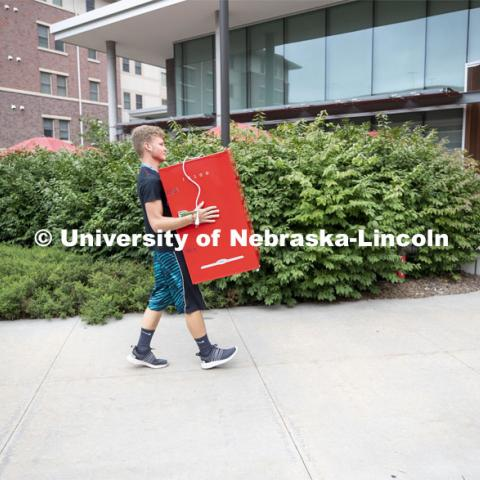 Jeremy Schepler of Wilcox, Nebraska, carries a refrigerator into Knoll Residence Hall. Jeremy is a freshman in the Honors program. Residential hall move-in to the Knoll Residential Center and University Suites. August 22, 2019. Photo by Craig Chandler / University Communication.