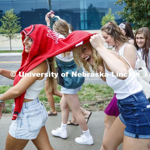 Valerie Bohuslavsky of David City, NE, shares her hoodie with Savannah Gerlack of DeWitt, NE, as the two try to keep dry as they walk in the rain between the Rho Gamma Reveal and the Bid Day activities. Sorority Bid Day. August 24, 2019. Photo by Craig Chandler / University Communication.