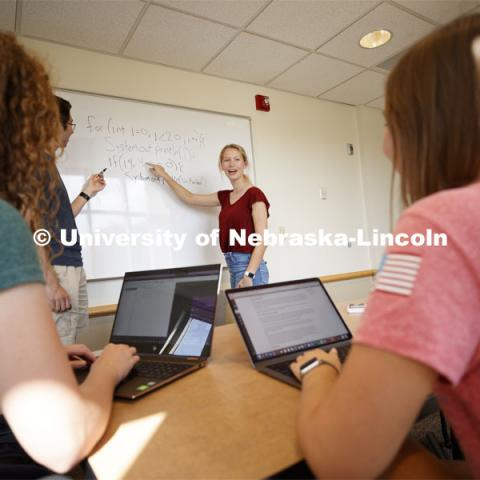 Students studying in a classroom, working through a problem on the marker board. Raikes school photo shoot. September 25, 2019. Photo by Craig Chandler / University Communication.