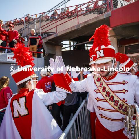 Band members high-five as they pass one another. Nebraska vs. Northwestern University football game. Homecoming 2019. October 5, 2019.  Photo by Craig Chandler / University Communication.