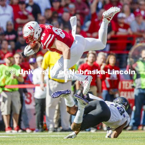 Nebraska's Jack Stoll goes airborne over a Northwestern defender in the first quarter. Nebraska vs. Northwestern University football game. Homecoming 2019. October 5, 2019.  Photo by Craig Chandler / University Communication.