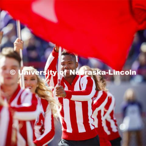 The Cheer Squad run across the field carrying flags that spell NEBRASKA. Nebraska vs. Northwestern University football game. Homecoming 2019. October 5, 2019.  Photo by Craig Chandler / University Communication.