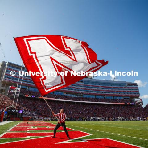 A male cheerleader squad member waves a giant N flag. Nebraska vs. Northwestern University football game. Homecoming 2019. October 5, 2019.  Photo by Craig Chandler / University Communication.