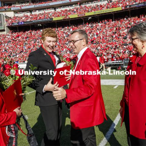 Seniors Cheyenne Gerlach and Bryce Lammers laugh with Chancellor Ronnie Green and Jane, his wife, after the halftime ceremony of the Nebraska-Northwestern football game. Nebraska vs. Northwestern University football game. Homecoming 2019. October 5, 2019.  Photo by Craig Chandler / University Communication.