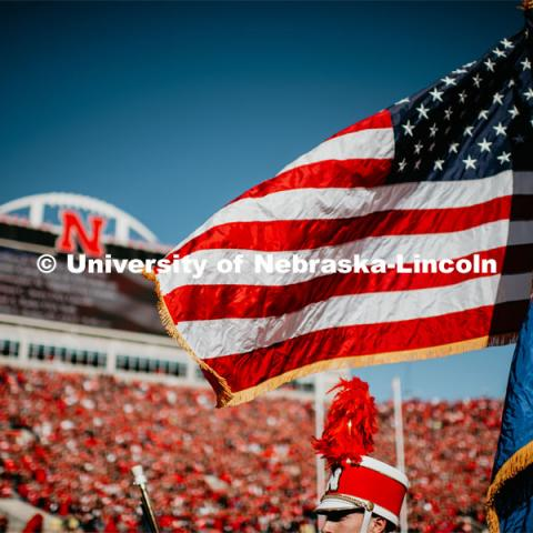 The United States and Nebraska Flags billow in the breeze with the Jumbo Tron in the background. Nebraska vs. Indiana University football game. October 26, 2019. Photo by Justin Mohling / University Communication.