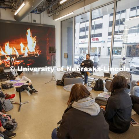 Hot learning on a cold day. Video of a fireplace takes the chill off as Jesse Fleming leads a discussion during his EMAR 140 - Visual Expression Studio course in the Johnny Carson Center for Emerging Arts. Snow on campus. October 30, 2019. Photo by Craig Chandler / University Communication.