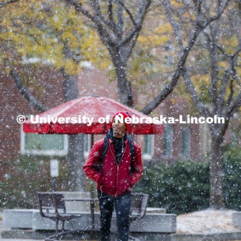 Paul Muragizi, senior in sociology from Lincoln, walks across the plaza during the snow. Snow on campus. October 30, 2019. Photo by Craig Chandler / University Communication.