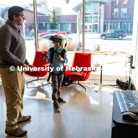 Young boy is being shown how to use the HP Backpack VR set at the Carson dedication ceremony. Johnny Carson Center for Emerging Media Arts dedication weekend. November 17, 2019. Photo by Justin Mohling / University Communication.