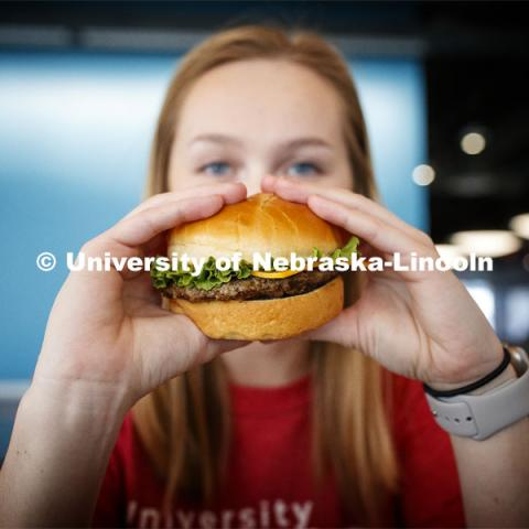 Cather Dining Center photoshoot. Young woman holding a burger in front of her face. March 2, 2020 Photo by Craig Chandler / University Communication.