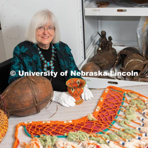 Priscilla Grew, director emerita, admires objects in the University of Nebraska State Museum's African collection, including a horse breast collar purchased in Egypt. She holds a basket from Ethiopia collected about 1960. Also in the photo are a large basket from Sudan and a gourd from Tanzania. February 26, 2020. Photo by Greg Nathan / University Communication.