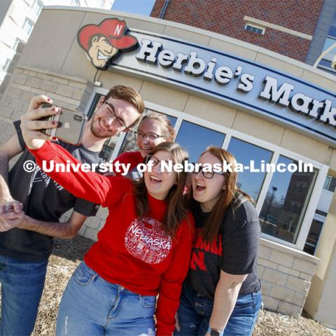 Harper Dining Center photo shoot. Students snap a selfie outside Herbie's Market near Harper Dining Center. March 3, 2020. Photo by Craig Chandler / University Communication.