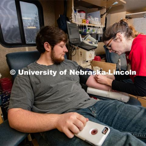 Kelsey, of the Community Blood Bank, preps Student Ryan Wiese of Grand Island, an Agribusiness Senior, to donate Blood. March 9, 2020. Photo by Gregory Nathan / University Communication.