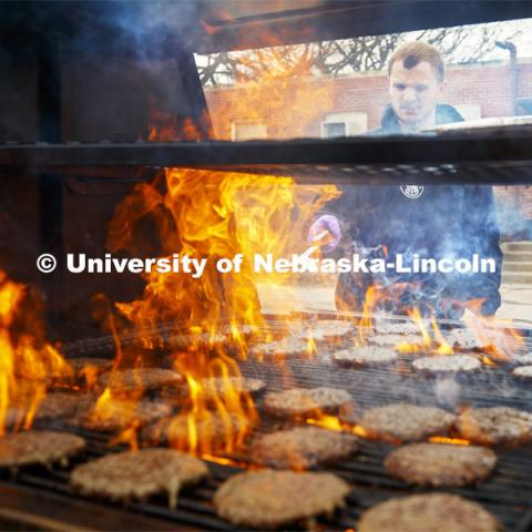 Dan Serdar, junior in Animal Science from Spring Grove, Illinois, flips hamburgers being grilled outside the Animal Science building. Lunch In The Lobby in the Animal Science building lobby is part of CASNR week. March 11, 2020. Photo by Craig Chandler / University Communication.