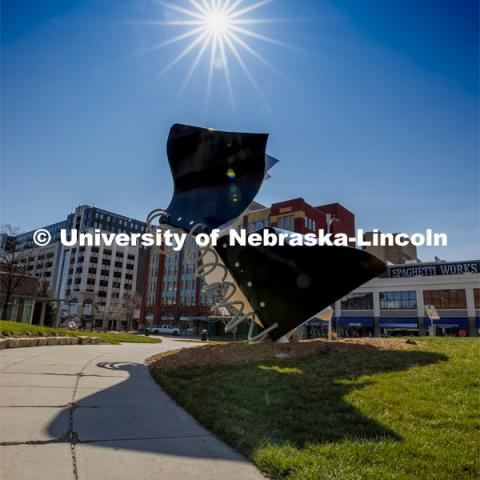 The sun shines in the blue sky above the Torn Notebook sculpture on city campus. March 30, 2020. Photo by Craig Chandler / University Communication.