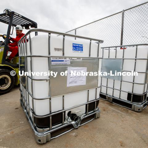 Russell Parde drives a forklift after lowering a container of hand sanitizer after it was emptied into smaller jugs. Hand sanitizer is being made at Nebraska Innovation Campus thanks to a collaboration between the Food Innovation Center and the Nebraska Ethanol Board. April 6, 2020. Photo by Craig Chandler / University Communication.