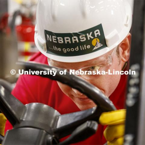 Russell Parde peers under the pallet of non-flammable ingredients as he steers it into place inside Food Innovation Center. The ingredients will be mixed with the ethanol in an outdoor area under stringent safety rules. Hand sanitizer is being made at Nebraska Innovation Campus thanks to a collaboration between the Food Innovation Center and the Nebraska Ethanol Board. April 6, 2020. Photo by Craig Chandler / University Communication.