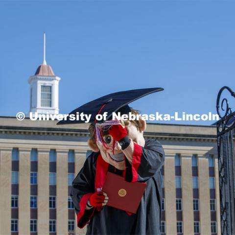 Herbie Husker turns his tassel in front of Love Library, and is decked out in graduation attire for the Spring Commencement that was which streamed online and aired on NET because of the COVID-19 pandemic. April 10, 2020. Photo by Craig Chandler / University Communication.